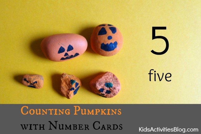 Cute painted pumpkin rocks used for the counting pumpkin games with the number card that has circles