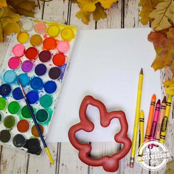 Paints, leaves cookie cutters, pencils, paper, and crayons about to make warhol inspired fall leaf art project.