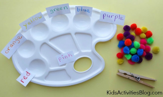 Fun color matching game that doubles as a fine motor skill game for preschoolers using paint palettes, pom poms of many colors, and a clothes pin.