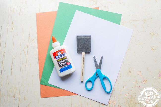 kids irish flag craft supplies - shown orange, green and white paper, glue, sponge and scissors