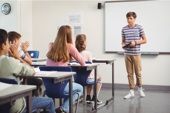 Public speaking games for kids to improve confidence - teen boy giving class presentation - Kids Activities Blog