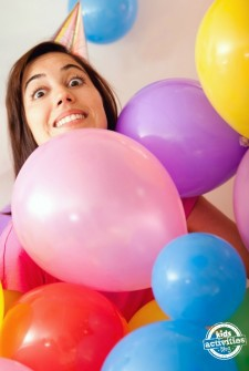 Woman at a birthday party surrounded by colorful balloons