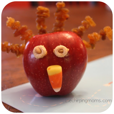 Apple turkey snack creation with dried fruit sticking out of it, cereal eyes, and a candy corn nose.