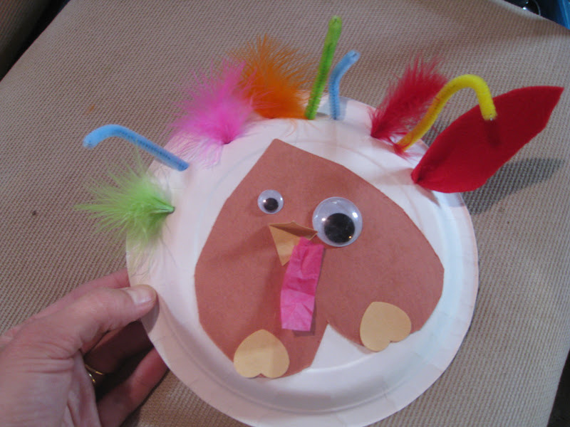 Paper plate turkey craft with construction paper, googly eyes, pipe cleaner, and feathers.