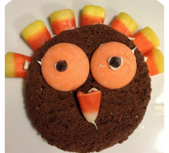 No bake turkey Thanksgiving cookie with candy corn as feathers, orange candy as the eyes, and a candy corn nose.