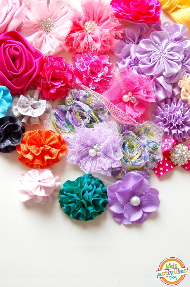 Assortment of finished ribbon flowers with different types of embellishments like pearls, diamonds and more - all bright colors