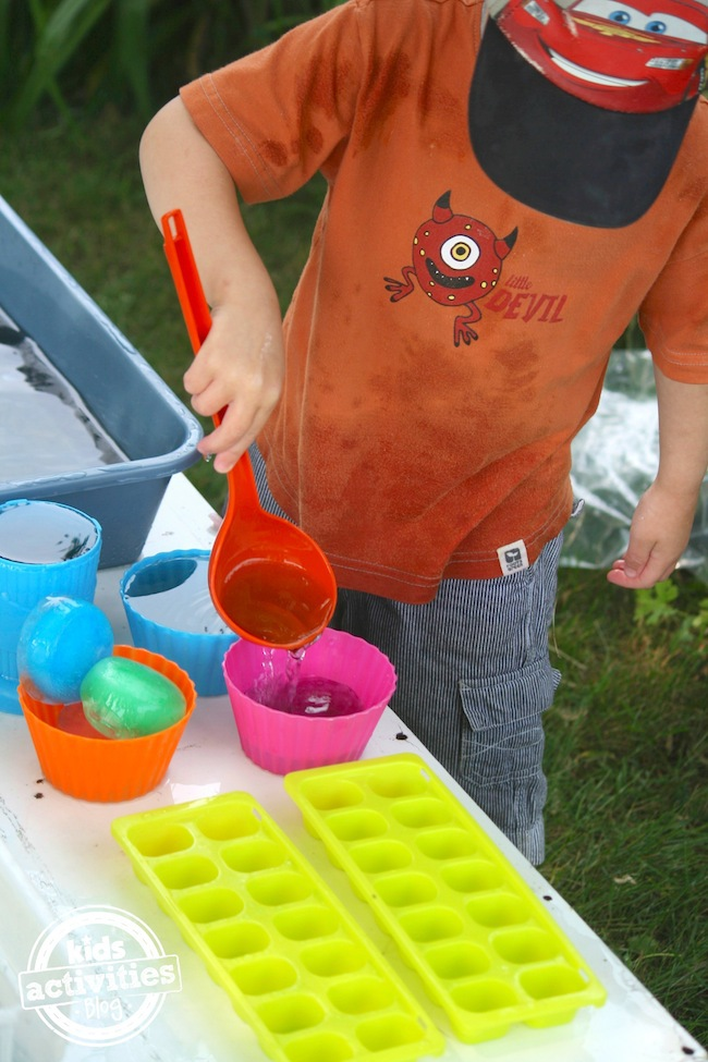 scooping and pouring from coloured ice activity bin