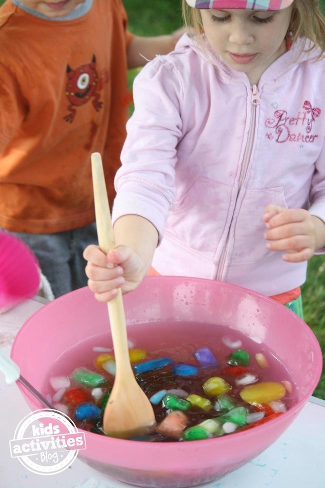 en remuant de la glace colorée dans un bol d'eau