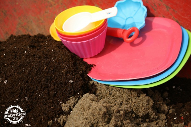plastic dishes, sand, soil in wheelbarrow