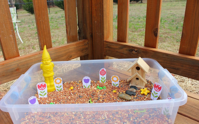 Plastic bin full of bird seed, a bird house, and various garden toys sitting on a wooden porch.