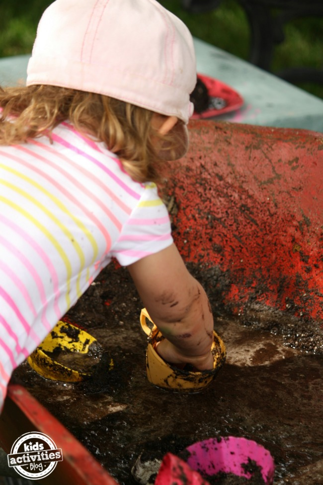 child digging in mobile mud kitchen