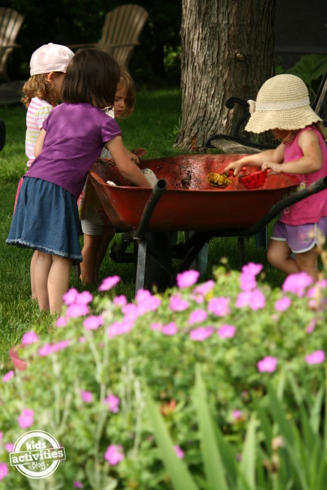 kids playing in mud-filled wheelbarrow
