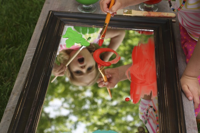 painting on a mirror under canopy of leaves