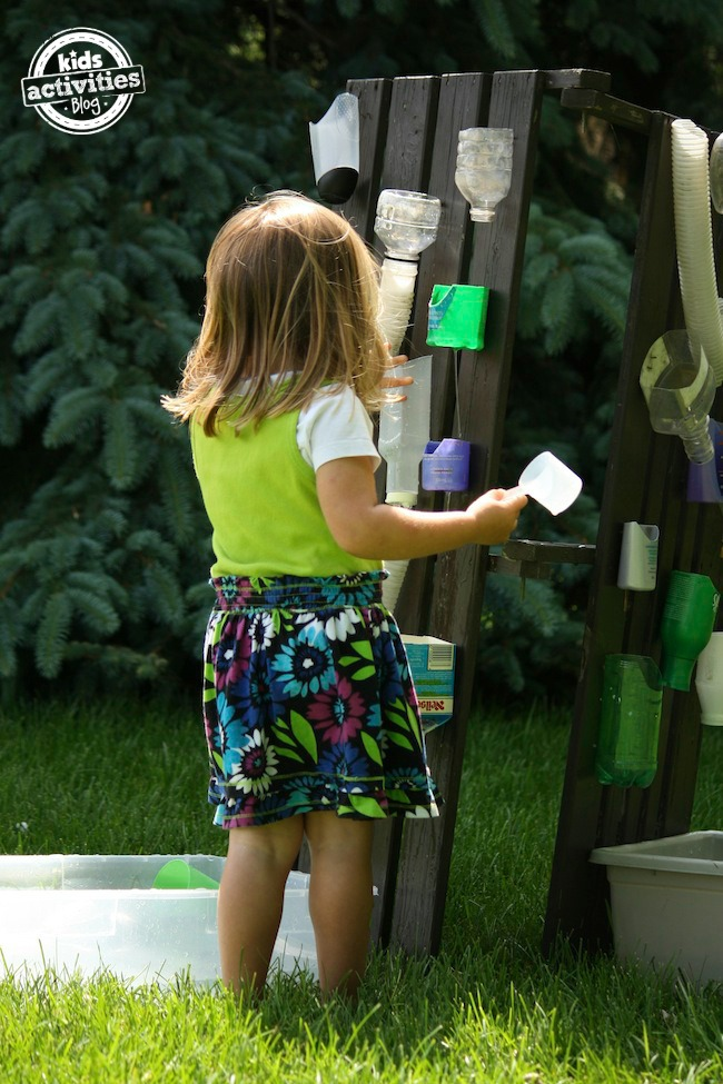 water wall for kids - water wall shown with multiple containers attached to wooden vertical surface fence and child with cup in hand