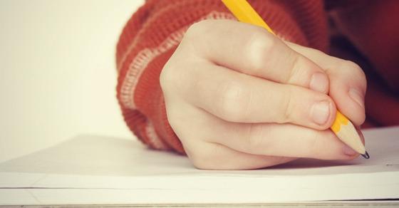 Mauvaise façon de tenir un crayon - position incorrecte courante que les enfants utilisent souvent - quatre doigts serrent le crayon au lieu de trois - montré en train d'écrire de manière incorrecte sur du papier de cahier