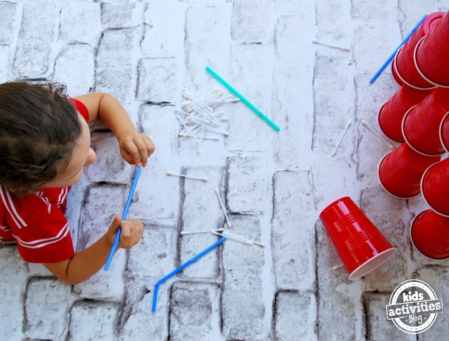 knock down a cup tower with straw darts.