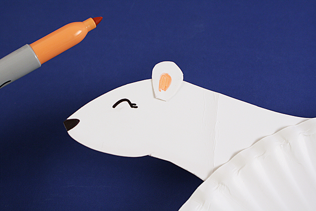 Use a glue stick to attach the ear to the head.