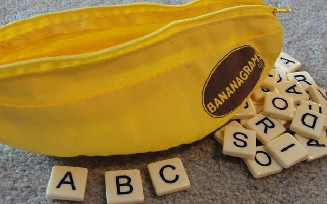 Bananagrams sight word activity with Bananagrams pack and letters scattered around it.
