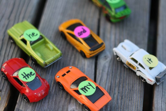 Drag race sight word game with sight words written on small stickers and placed on small car toys on a wooden background.