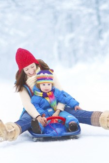 Young mother and her little toddler daughter enjoying a sledge r