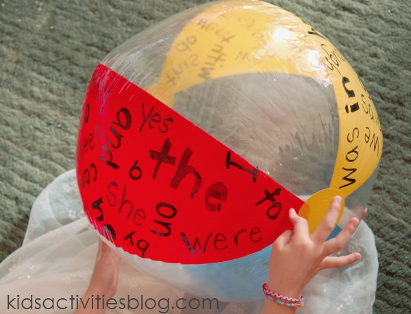 Beach ball sight word game with little kid holding a colorful beach ball that has sight words written on it.