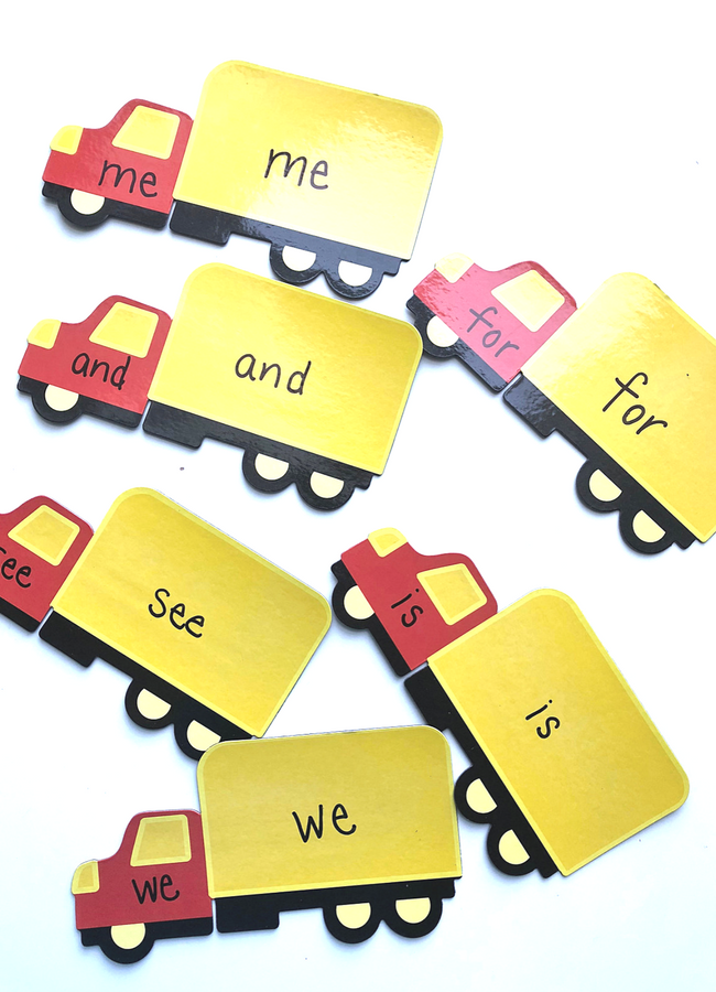 Truck magnet sight word game with sight words written on yellow and red truck magnets.