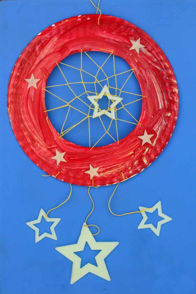paper plate dream catcher craft for kids - red dream catcher on blue background
