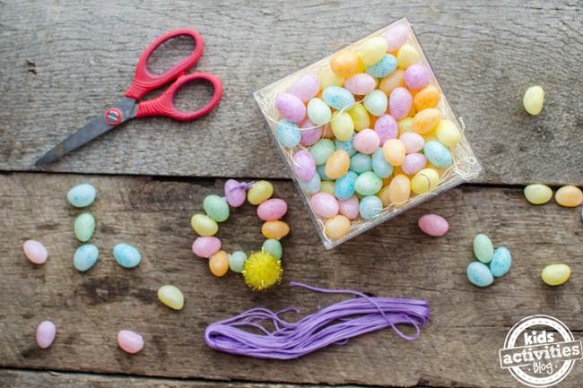 bracelet de fèves à la gelée fait maison avec des ciseaux rouges, des fèves à la gelée et de la ficelle violette.