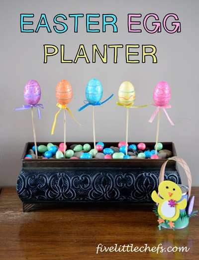 Easter Egg Decorations are made from foam Easter eggs on a stick and placed within a planter pot with rocks, foam, and candy eggs