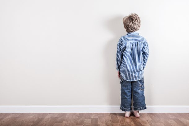 If Your Toddler Is Being Too Rough - discipline is a difficult solution - boy standing at wall in time out