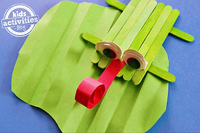popsicle stick frog craft on a paper lily pad with a curly red tongue, googly eyes, and is green.