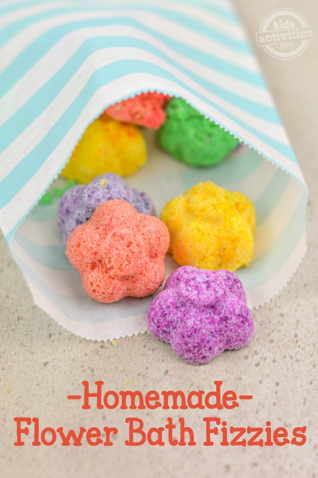 Homemade Flower Bath Fizzies in a paper bag that is white and blue and the fizzies are purple, pink, yellow, and green flowers.