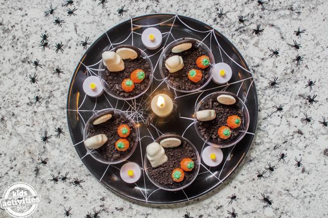 tasses de pudding d'halloween disposées sur un plateau d'en haut avec des bougies