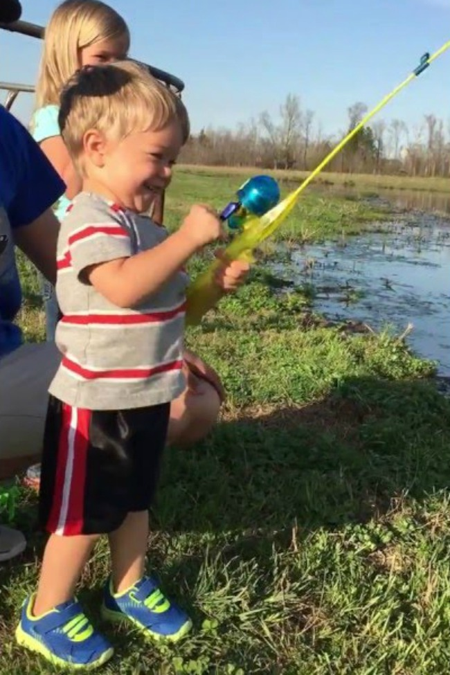 Little boy unexpectedly catches fish with toy rod for Little boy fishing
