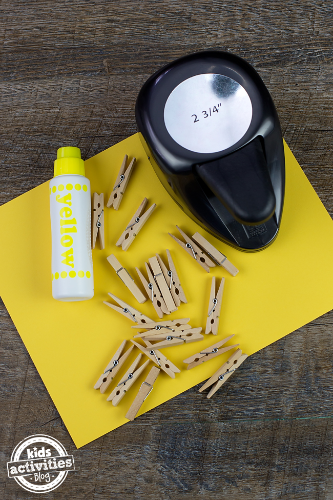 Suministros de artesanía necesarios para esta manualidad soleada como pinzas para la ropa, papel de construcción, un marcador de punto amarillo y una perforadora.