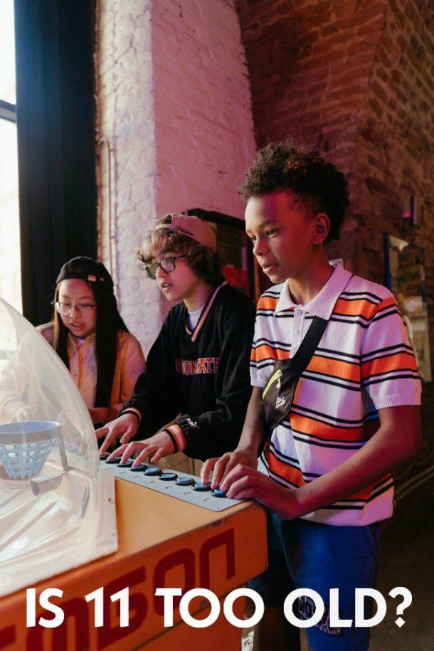 Three tweenage kids playing arcade games.