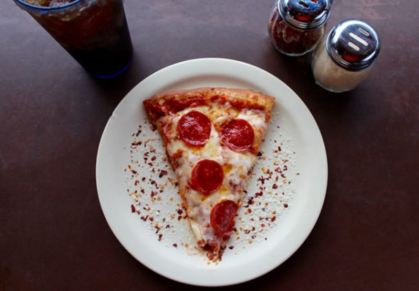 A white plate with a slice of pepperoni pizza on it. A drink to the left and parmesan cheese and peppers to the right, all on a dining table.
