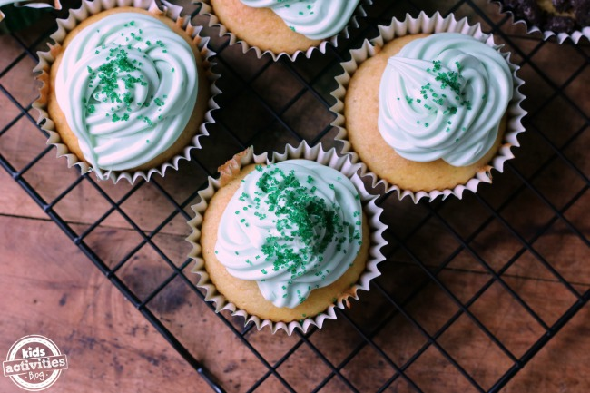 How to make earth cupcakes with blue frosting, green sprinkles, and vanilla cupcake base in liners on a rack.