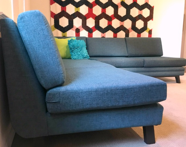 blue Joybird sectional with two throw pillows on it