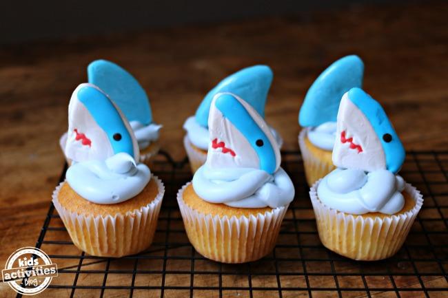 Cupcakes de tiburón con glaseado azul que parece agua y adornos de gomitas de tiburón