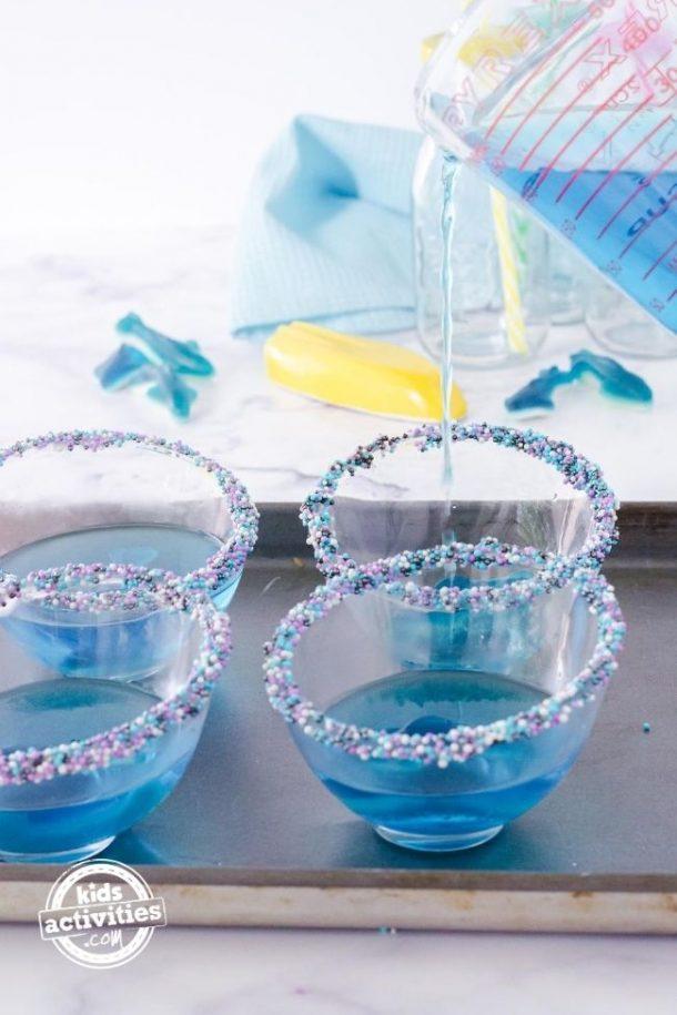 Se vierte gelatina azul en las tazas de postre de tiburón gomoso.