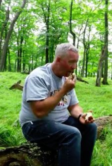 Man Sits In A Field, Calmly Eating Apples And Completely Surrounded By Wild Deer