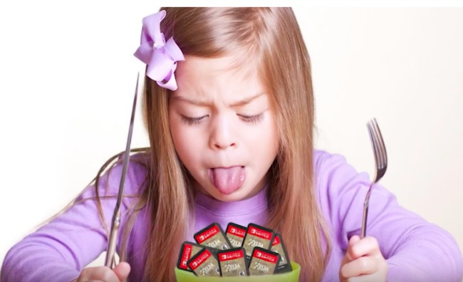 child sitting down in front of a bowl of nintendo switch cartridges to eat