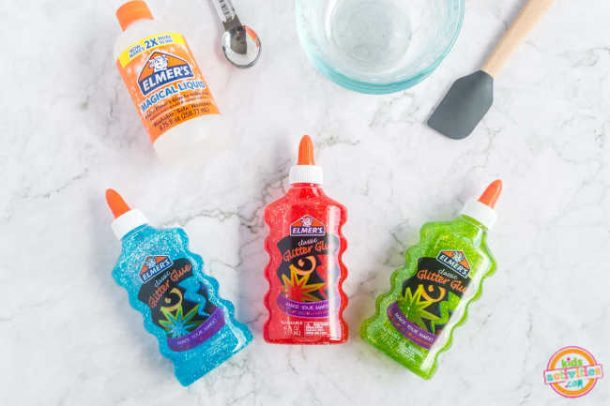 supplies for making colorful slime like elmers glitter glue magical liquid , measuring spoon, bowl and spatula displayed on a marble background