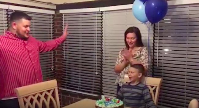screenshot of boy at birthday party looking at his dad