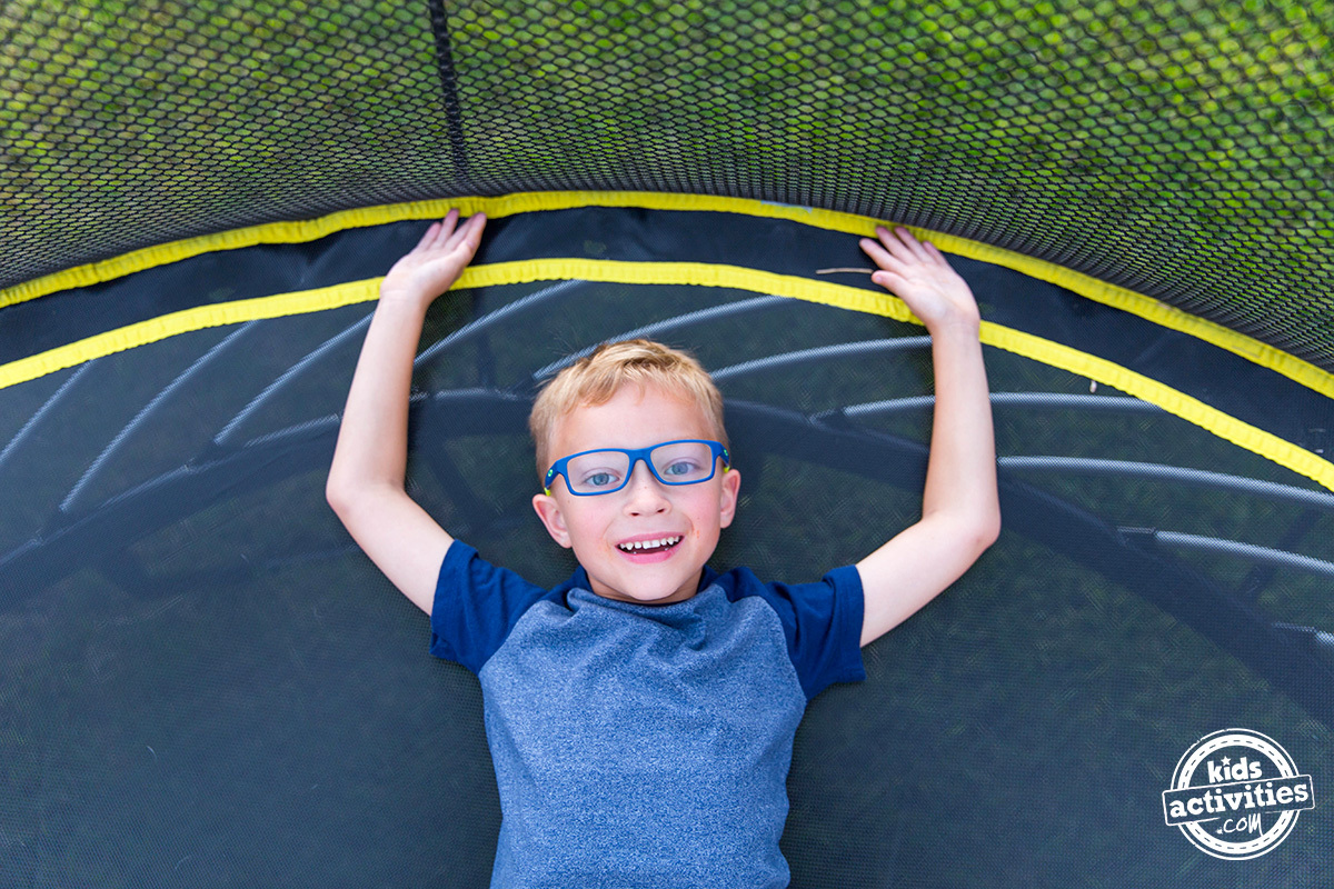 boy laying on springfree trampoline