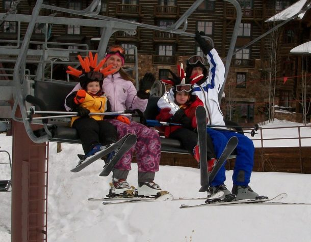 family riding ski lift in colorado