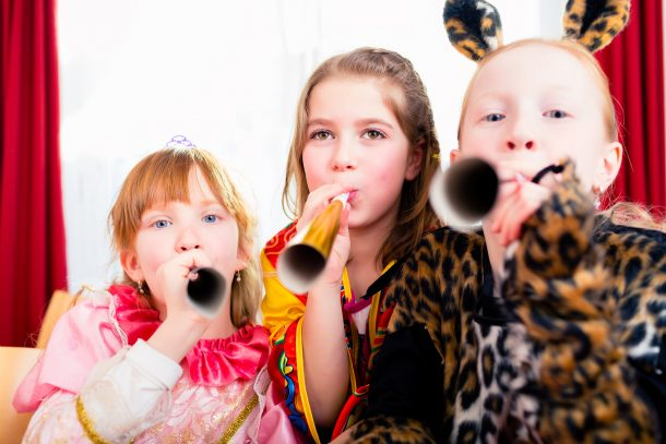 New years eve party themes 2021 with activities, foods, kids blowing noise makers, and more