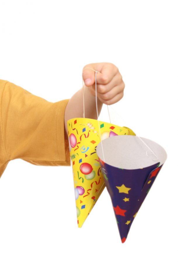 New Years party ideas, a boy holding two party hats yellow and blue.