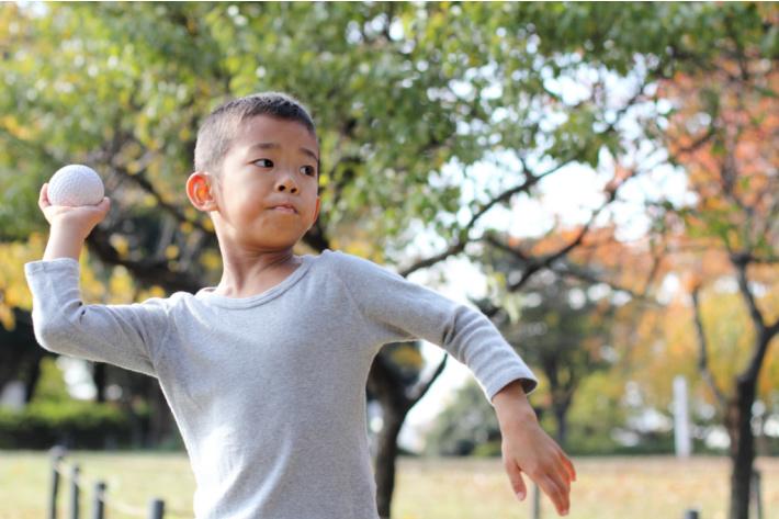 Enfant qui lance la balle au-dessus de la tête - stabilité des bras - Blog d'activités pour enfants